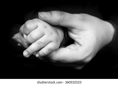 Black and white photo of hand of mother holding heir baby's small