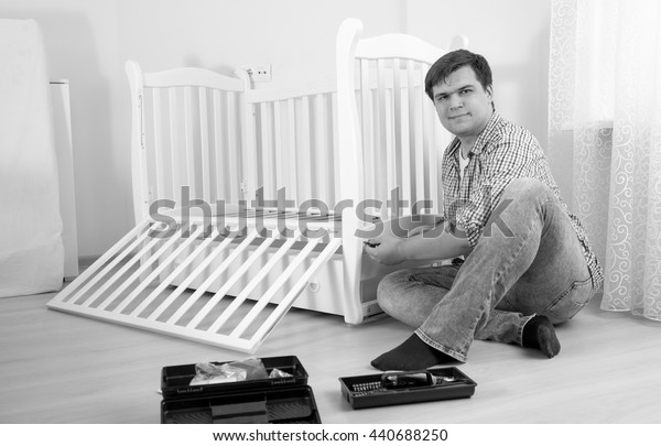 Black and white photo of handyman sitting on floor and assembling furniture in nursery