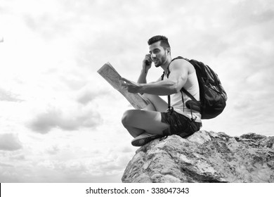 Black and white photo. Hiker portrait. Explorer talking via radio station. Young man tourist with a backpack sitting on top of a mountain and holding map