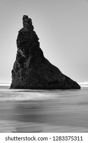 Black and White photo of Howling Dog rock on the beach in Bandon, Oregon with a wave rushing through the foreground.