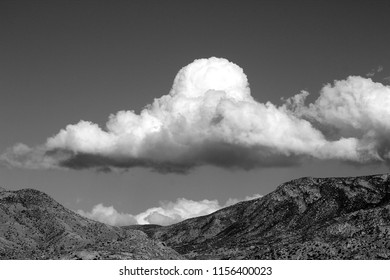 Black and white photo of huge puffy white monsoon clouds framing the Samta Catalina Pusch Ridge mountains on a sunny day in the Tucson Arizona desert