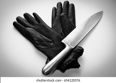 A black and white photo of a  knife(murder weapon) and a two gloves on a plain background. This image can also be used to represent crime scene evidence.