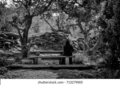 Black and white photo of a lady dressed in black sitting lonely on a bench in a forest facing the trees. Photo captured in Saudi Arabia, Middle East.