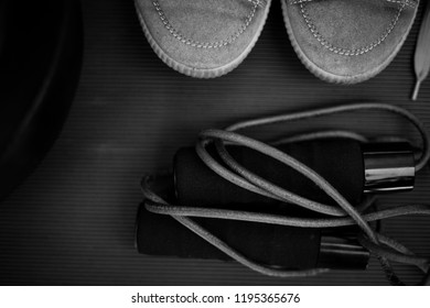 black and white photo of a leather skipping rope and a pair of vintage trainers