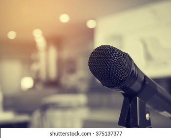 Black and white photo and lighting of the black microphone in concert hall or conference room with defocused bokeh lights in background. Extremely shallow dof. : Vintage style and filtered process.