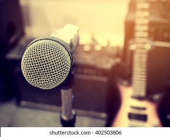 Black and white photo and lighting of The microphone in a recording studio or concert hall with amplifier and  electric guitar in out of focus background. : Vintage style and filtered process.