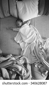 Black and white photo of little baby boy sleeping on parents bed
