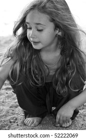 Black and white photo of a little girl with long hair playing in the sand