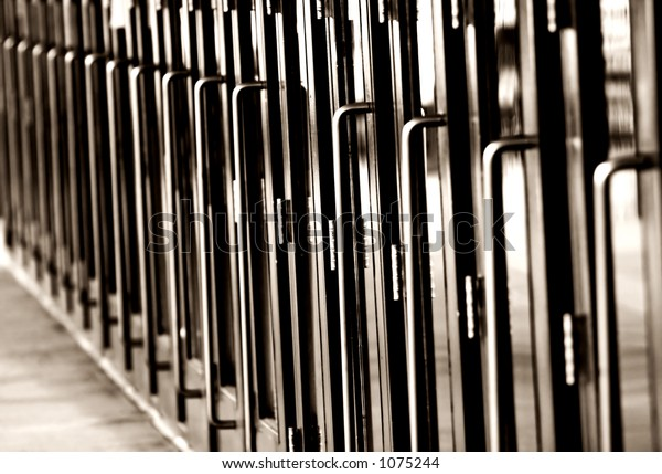 Black & White photo of a long line of steel and glass doors with metal handles (shallow focus).