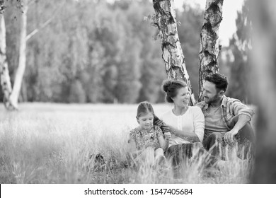Black and white photo of lovely family sitting under the tree while having picnic