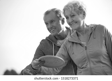 Black and white photo of Loving active couple throwing flying disc together in park