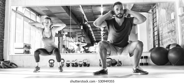 Black and white photo of a man and woman working out at gym.