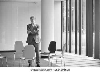 Black and white photo of mature businessman standing with arms crossed in office