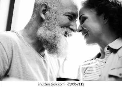 Black and white photo of mature couple touching foreheads and smiling at each other