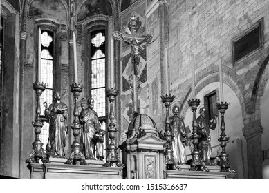 Black and white photo of metal statues of saints decorating altar in catholic church