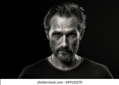 Black and white photo of mid aged man showing severe emotion. Beardy male in black t-shirt on dark background with serious look.