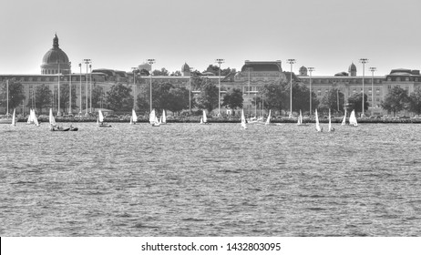 Black & white photo of midshipmen in sailboats training to be sailors on the Chesapeake Bay. Historic buildings of the Naval Academy in Annapolis line the horizon. The chapel dome rises high above.