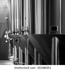 Black and white photo of modern brewery equipment with stainless tanks for the fermentation beer
