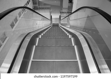 black and white Photo modern escalator in shopping center. Escalator at an airport with no people. escalators in symmetry going up and down.