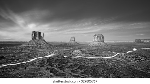 Black and white photo of the Monument Valley with car lights trails at night, USA.