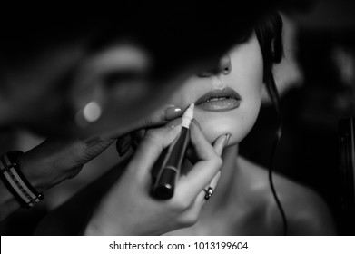 Black and white photo. Morning of the bride. Dresses, gathers, puts on makeup. Hotel room. Wedding details. She dabs his lips with lipstick.