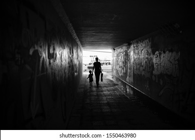Black and white photo of mother with baby in underpass with graffiti
