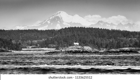 A black and white photo of Mount Baker with a sailboat and a small house in the forefront, near San Juan Island.