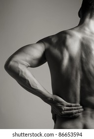A black and white photo of a muscular man holding his lower back as if experiencing a backache.