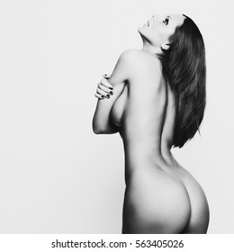 Black and white photo of nude sexy beautiful woman. Perfect naked body of sexy lady. Beautiful woman shows her nude body. Sexy nude brunette with beautiful booty