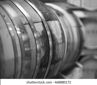Black and white photo of oak whiskey barrels sitting on barrel racks, while aging whiskey