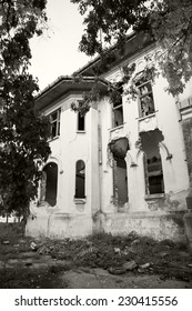 Black and white photo of an old, abandoned, ruined house with beautiful details
