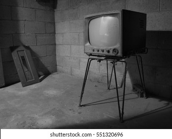 A black and white photo of an old TV from the 1950s forgotten and abandoned in a basement.