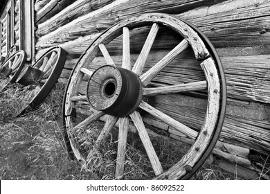Black & White photo of old wagon wheels leaning against log building.