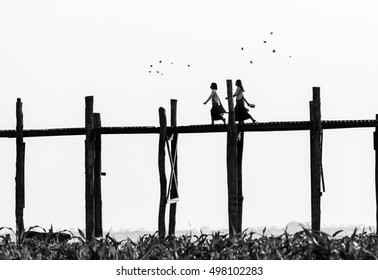 Black and white photo of old wooden bridge and silhouettes of two girls, U Bein Bridge is a crossing that spans the Taungthaman Lake near Amarapura, Myanmar