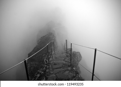 Black and white photo of the path to the Pico Ruivo and Pico do Arieiro mountain peaks in a fog in Madeira, Portugal. A mystic path, road to nowhere