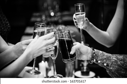 Black and white  photo of people holding glasses of wine and clinking