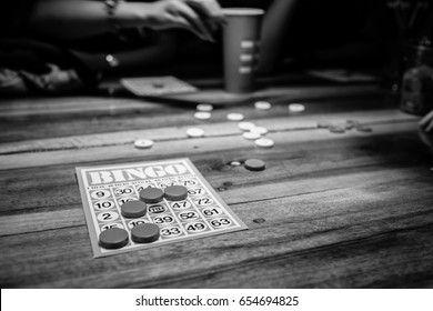 Black and white photo of people playing bingo game and having very much fun of bingo game playing on a wooden table. Bingo card on the wooden table and the  game of chance is played. Activity to do.