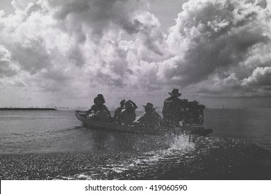 Black and white photo of people traveling in an engine boat