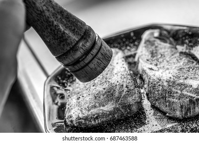 Black and white photo of a person seasoning two fresh looking ribeye steaks with pepper from a pepper mill