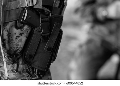 Black & white photo of pistol in holster on soldiers leg.Military man armed with semi automatic gun.Armed & dangerous soldier ready for war.American swat police member,national guard