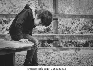 Black and white photo of poor little put head down and looking at his feet with sad face sitting alone at the park,kid boy with worrying face looking down, lost children or homeless kid concept