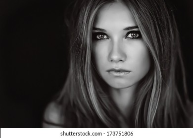 Black and white photo portrait of a girl who looks at the camera.
