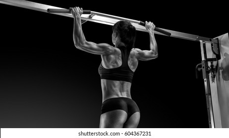 Black and white photo of professional Pull Up Workout Exercise Back Lats Muscles Pullups Pull torso up until the bar touches upper chest by drawing the shoulders and upper arms down and back.