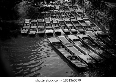 Black and white photo of punting boats by Magdalen Bridge Boathouse on river Cherwell in Oxford, many boats docked together in rows.