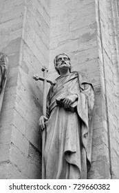Black and white photo of a saint holding a tall cross and a book on the facade of a church in Antwerp, Belgium. Statue of a saint on the exterior of a church in Europe.