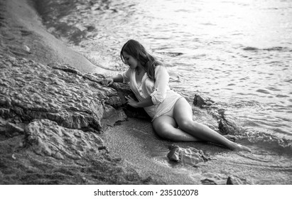 Black and white photo of sexy lonely woman lying on rocky beach