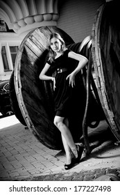 Black and white photo of sexy woman leaning against huge bobbin