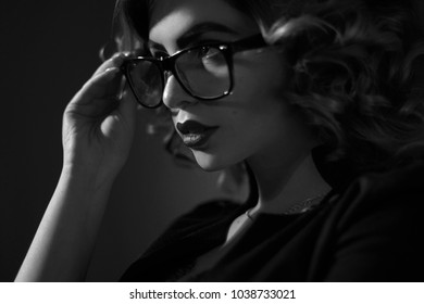black and white photo of Sexy young secretary in glasses and curly hairstyle in studio