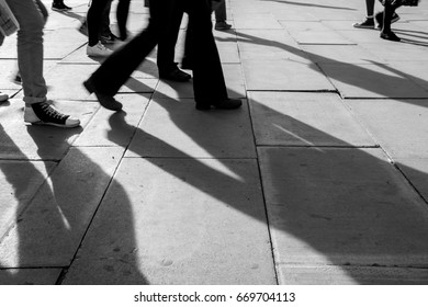 Black and White photo. Shadow of People walking on a street. Pedestrian walking in a footpath. Walking Shadow in the city.