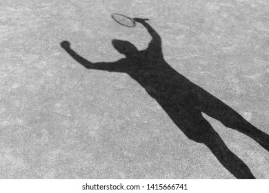 Black and White photo of Shadow of successful man standing with arms raised on red tennis court during match